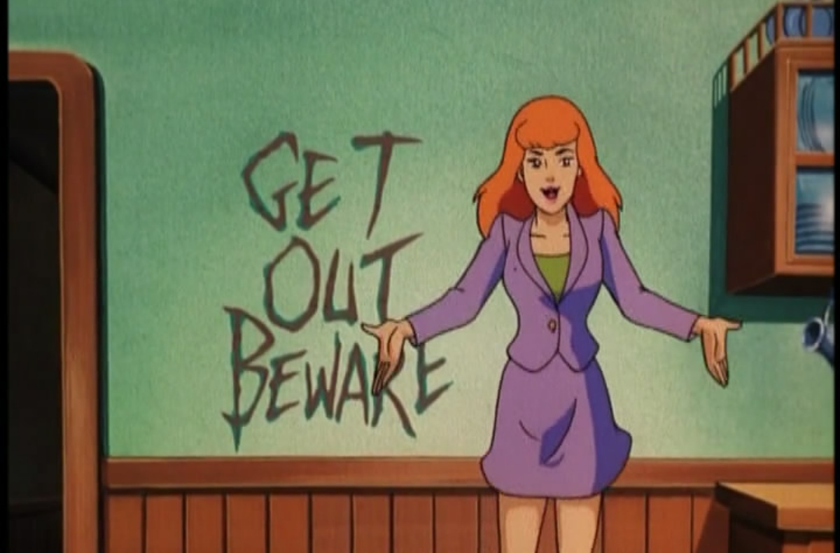 """Daphne in front of a wall with the carved out words """"get out beware."""""""
