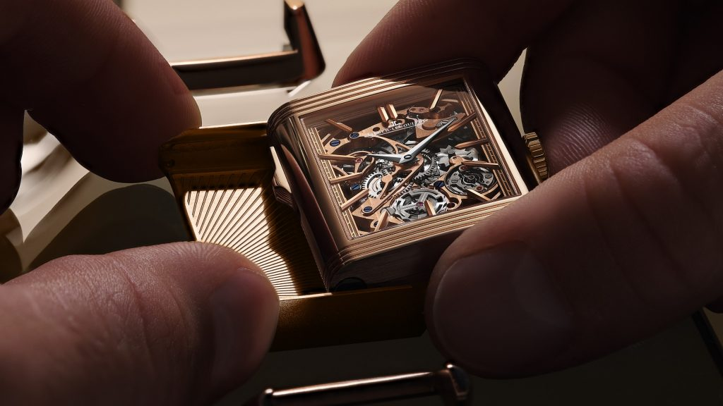 While the exuberance of the front dial contrasts with the rectilinear geometry of the Reverso case, the relative sobriety of the reverse dial echoes and amplifies those straight lines. Vertical Côtes de Genève stripes extend over the entire height of the main plate, which also serves as the dial. Showcasing the timekeeping mechanism, with subtle colour accents provided by blued screws and golden hands and hour markers, the cool silver tone of the metal provides an elegant counterpoint to the warm rose gold of the case.