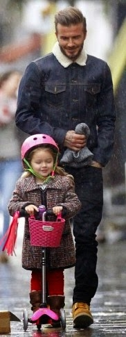 David Beckham looks on proudly as his daughter scoots through London