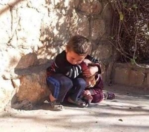 Heartbreaking photo of Syrian boy protecting his little sister from air strikes