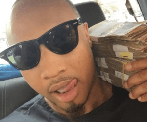 Singer B-Red poses with wads of Naira notes