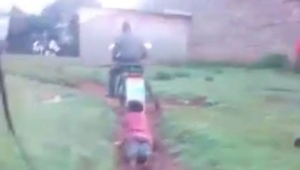 Policeman incites outrage after being filmed dragging a woman tied to his motorcycle on a dirt path (video)