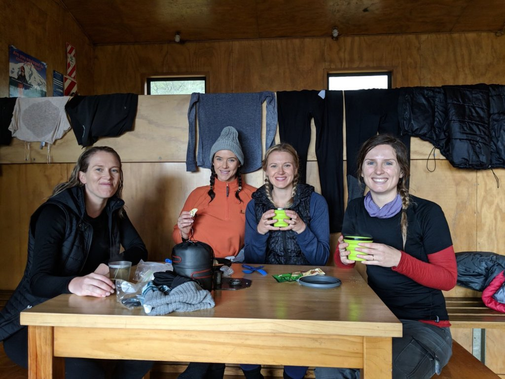 Soggy, Snowbound And Stoked // Routeburn Track (NZ), Rachel Dimond, Day 1 - Routeburn Falls Hut, girls, hikers, crew, friends, tea, rest stop, smiles, table