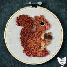 small embroidery hoop filled with white linen and a punch needle squirrel holding an acorn with a pink nose and a fluffy tail