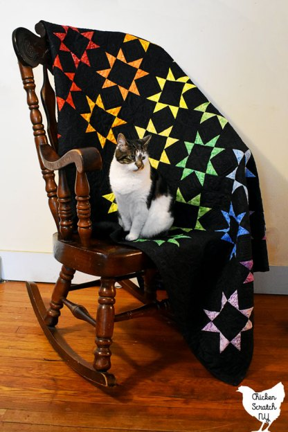 rainbow jelly star quilt sewn with batik fabric thrown over a rocking chair with a cat sitting on it
