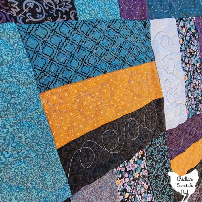 close up of rail fence block with loopy meander free motion quilting