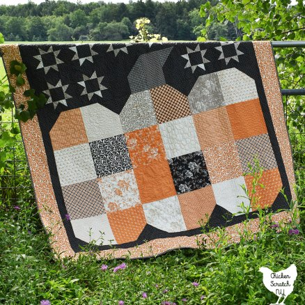 the great pumpkin throw quilt made with All Hallows Eve layer cake hanging over a fence