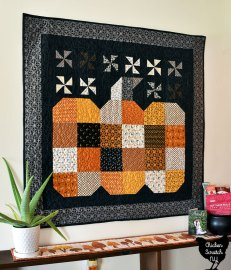 great pumpkin wall quilt made with Sleepy Hollow from Andover hung above a shelf with an aloe plant and autumn tree table runner