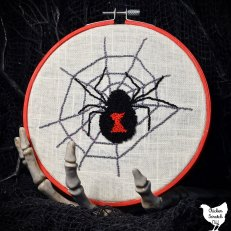 black widow punch needle embroidery pattern being held by a skeleton hand