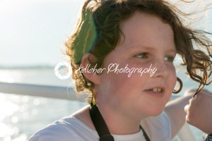 Beautiful young girl on boat at sunset with sun flare behind her - Kelleher Photography Store