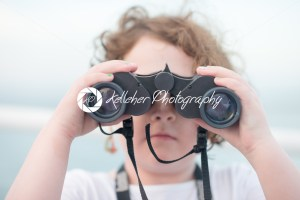 Beautiful young girl on boat looking directly at camera through binoculars - Kelleher Photography Store