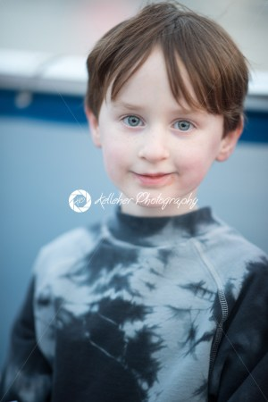 Young boy outside on boat looking happy - Kelleher Photography Store