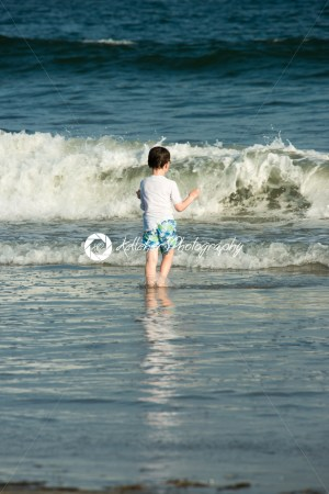 Young cute little boy playing at the seaside running into the surf on a sandy beach in summer sunshine - Kelleher Photography Store