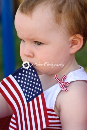 Young girl holding an American flag and riding in red wagon having fun in the park for July Fourth - Kelleher Photography Store