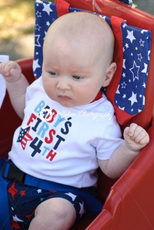 Young infant boy riding in red wagon having fun in the park for July Fourth - Kelleher Photography Store