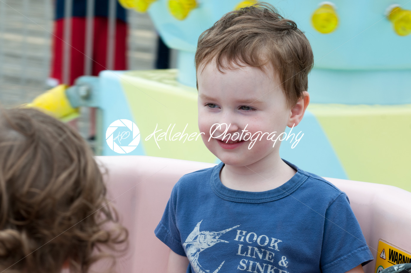 Young toddler boy having fun on boardwalk amusement ride - Kelleher Photography Store