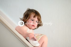 Portrait of a cute little girl inside on stairs holding dress show - Kelleher Photography Store