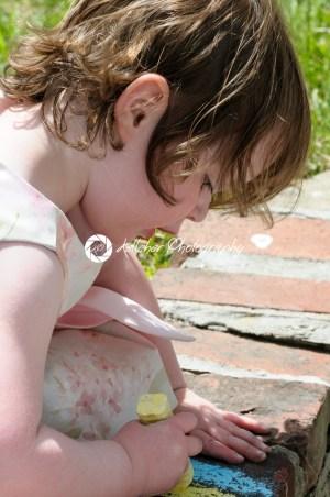 Portrait of a cute little girl outside writing on bricks with sidewalk chalk - Kelleher Photography Store