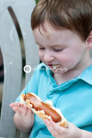Young boy outside eating a big hot dog - Kelleher Photography Store