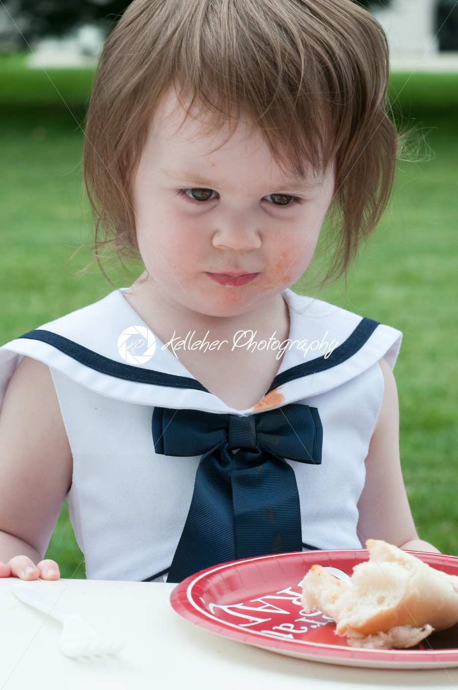 Young girl in fancy dress outside eating - Kelleher Photography Store