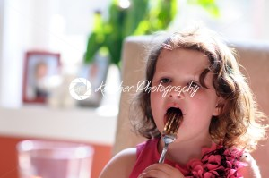 Young girl indoors eating birthday cake licking fork - Kelleher Photography Store