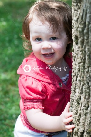 Young girl outside at park hugging standing next to tree - Kelleher Photography Store