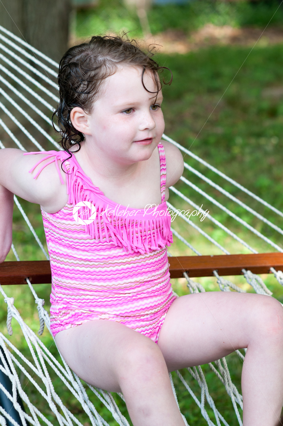 Young girl outside in swimming suit sitting on hammock - Kelleher Photography Store