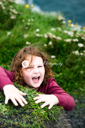 Girl looking up the Cliffs of Moher Tourist Attraction in Ireland - Kelleher Photography Store