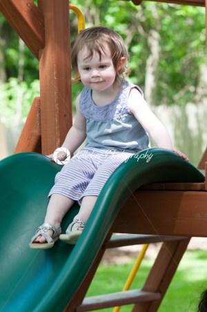Girl riding on childrens slides on playground - Kelleher Photography Store