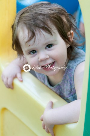 Little girl wearing summer dress looking out from plastic play house window in a playground - Kelleher Photography Store