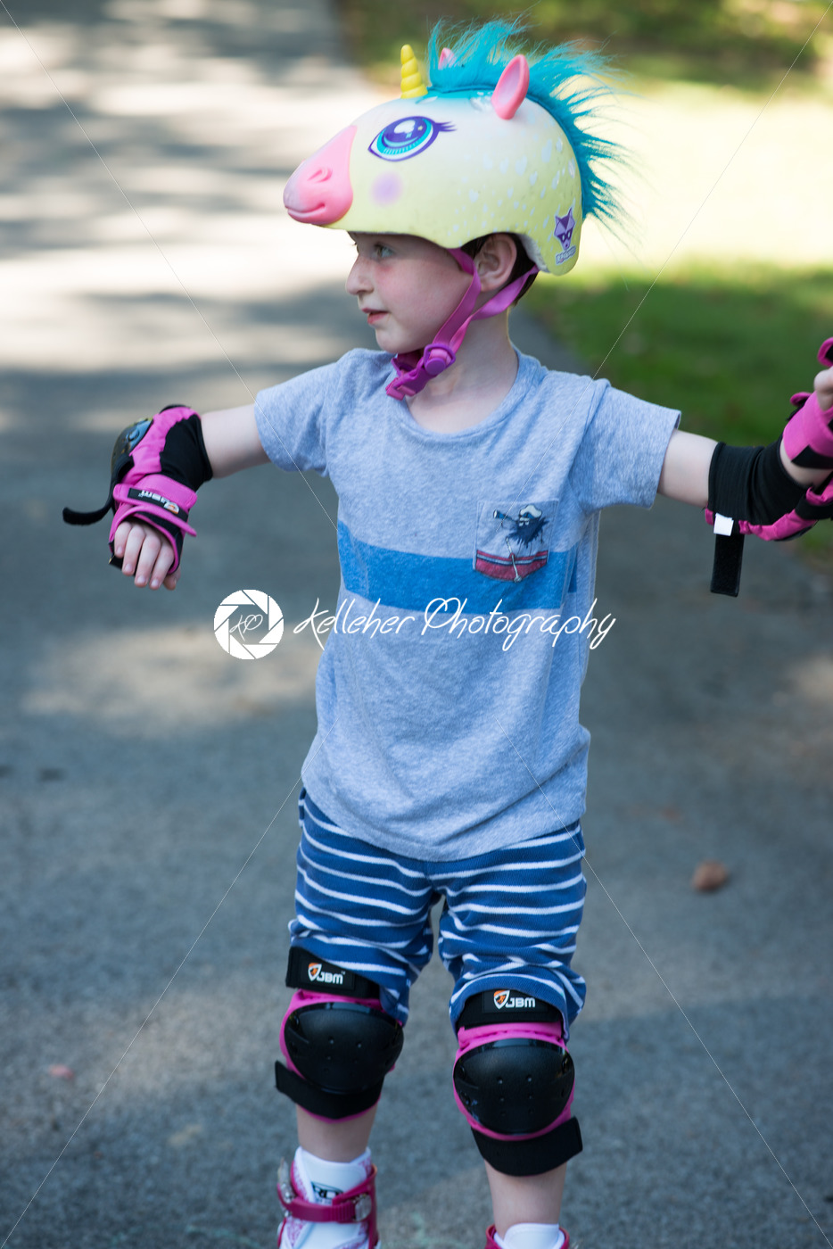 Young boy outside learning to riding on roller skates on driveway wearing protective helmet and elbow, wrist and knee pads - Kelleher Photography Store