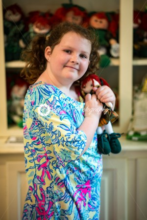 Young little Irish red-headed girl portrait looking and smiling at the camera holding doll that looks like herself - Kelleher Photography Store