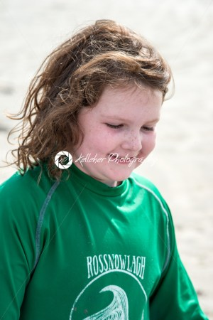 Young little girl on beach taking surfing lessons - Kelleher Photography Store