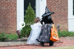 Little girls in witch and ghost costume having fun at Halloween trick or treat - Kelleher Photography Store