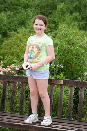 Preteen smiling girl standing on wooden bench - Kelleher Photography Store