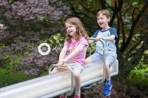 Two cute pre-school children sitting on a seesaw - Kelleher Photography Store