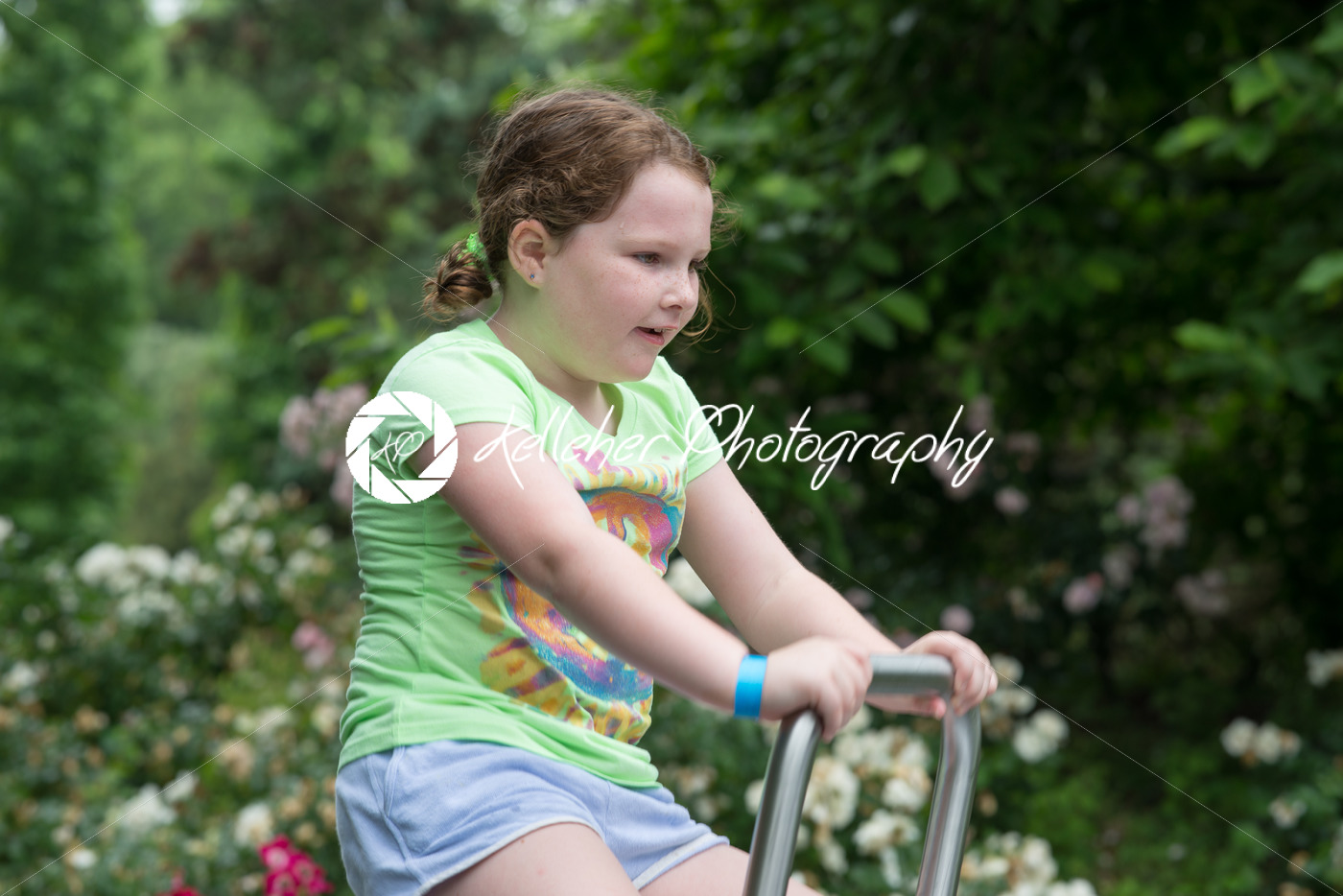 Young girl sat on ride in park - Kelleher Photography Store