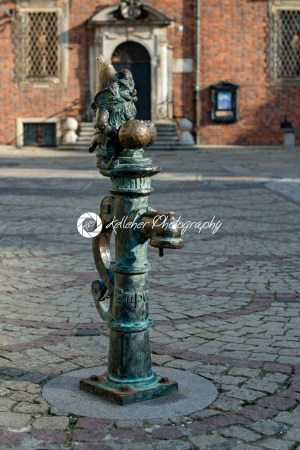 Wroclaw, Poland – March 4, 2018: Gnome on water pipe Wroclaw Market Square in evening in historic capital of Silesia, Poland, Europe. - Kelleher Photography Store