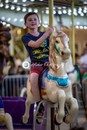 Happy young boy having fun on boardwalk amusement ride - Kelleher Photography Store