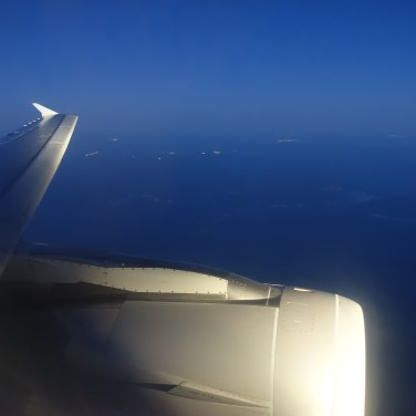 A jet engine and wing from out of the aircraft window