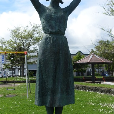Statue of girl with swing behind