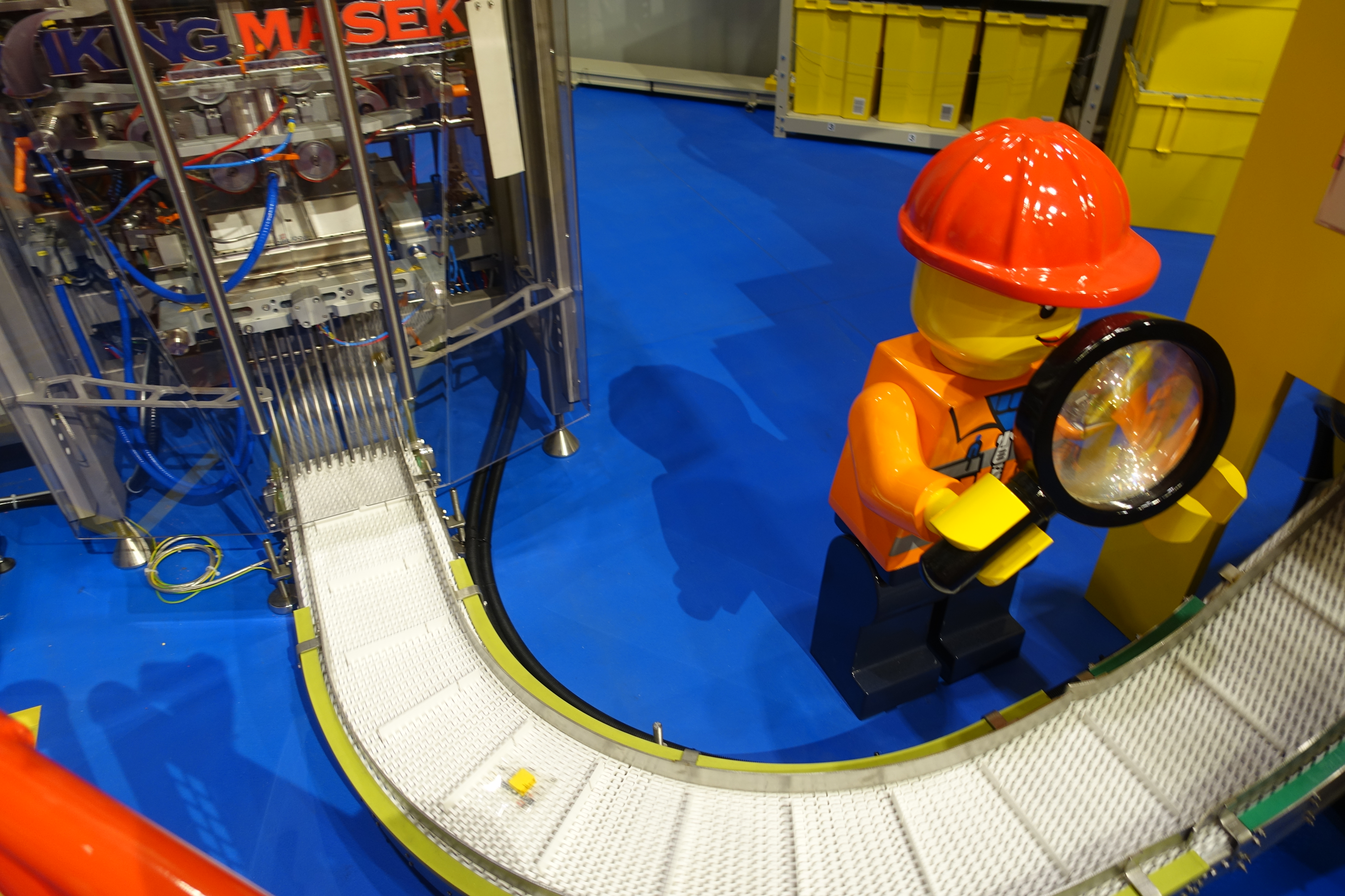 Giant Lego man inspecting a production line