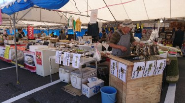 Grilled fish and other foods for sale under a tent