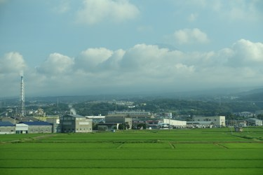 Mount Fuji behind rice paddies, factories and clouds