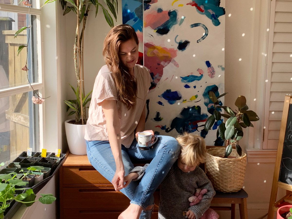 Painter Rachel Hawkes Cameron casaually sitting barefoot on a cupboard next to a large window, and plants, with her child by her knee. Two of her paintings are leaning against the wall in the background.