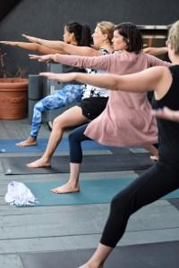Women in warrior post looking forward, knees bent, on yoga mat