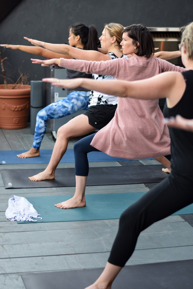 Women in warrior post looking forward, knees bent, on yoga mat