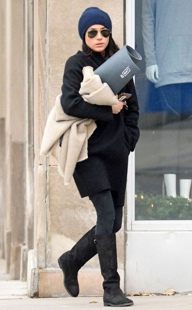 Megan Markle with hat on and glasses, in coat and boots, carrying a yoga mat and walking in front of a city building