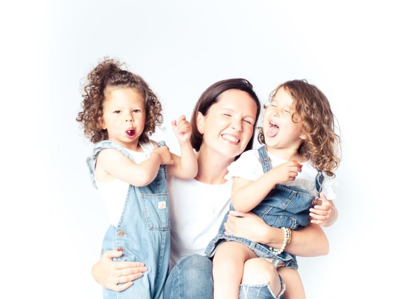 Female entrepreneur with brown hair, white t-shirt and ripped blue jeans, crouching down hugging her kids on both sides, two little girls