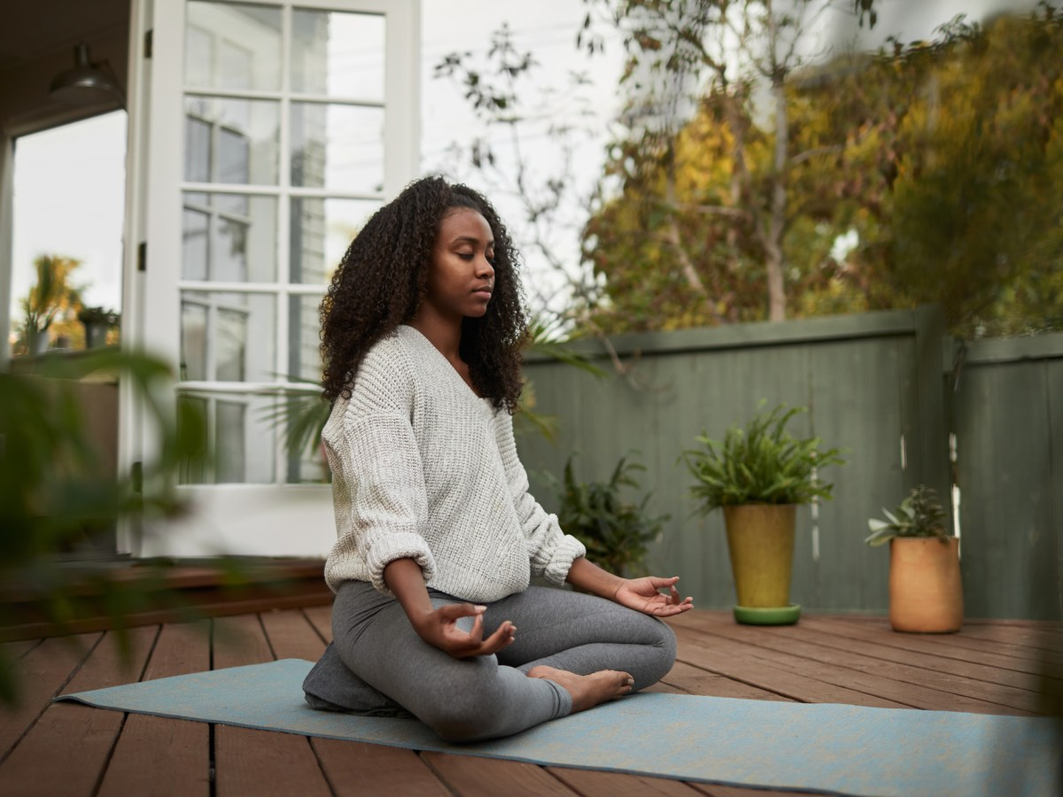 Young woman sitting in the lotus pose on a yoga mat outside on her patio on yoga mat, meditating